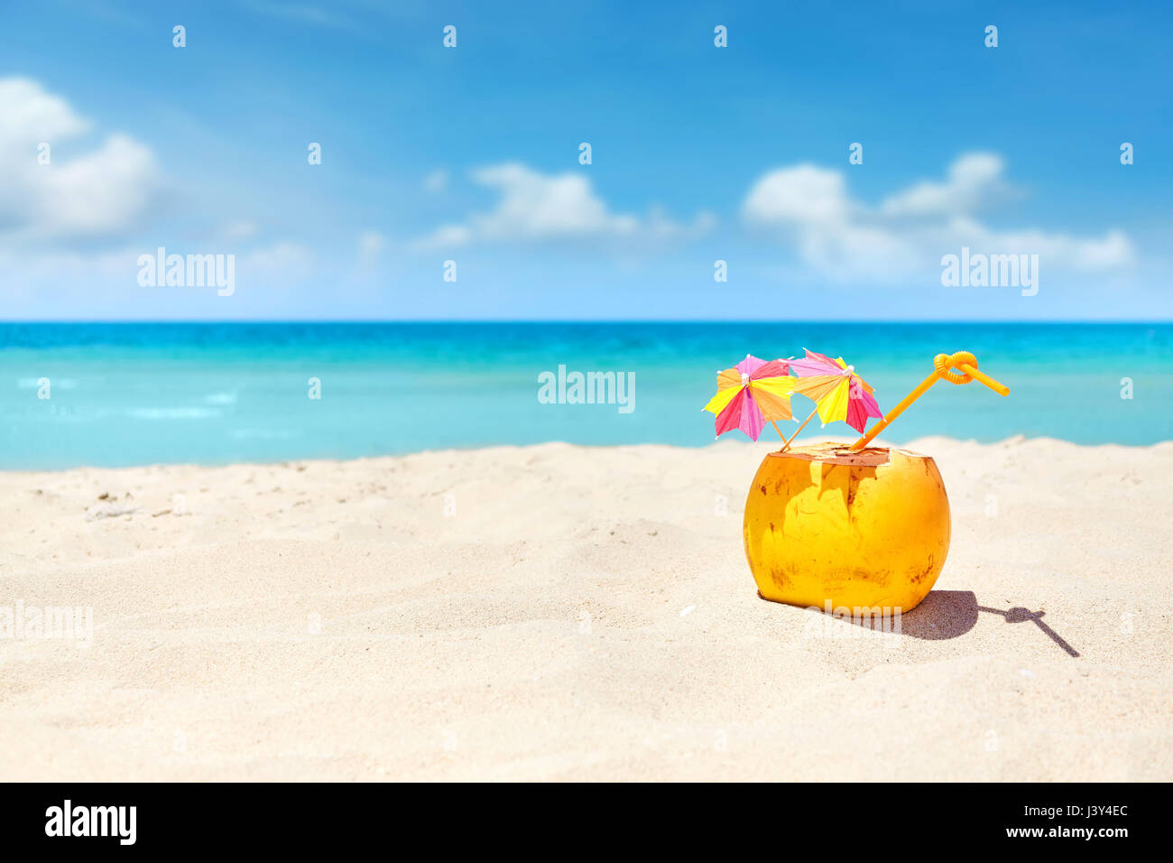 Coconut cocktail with straw and colorful umbrellas on a beach, summer holiday concept, selective focus, space for - Stock Image