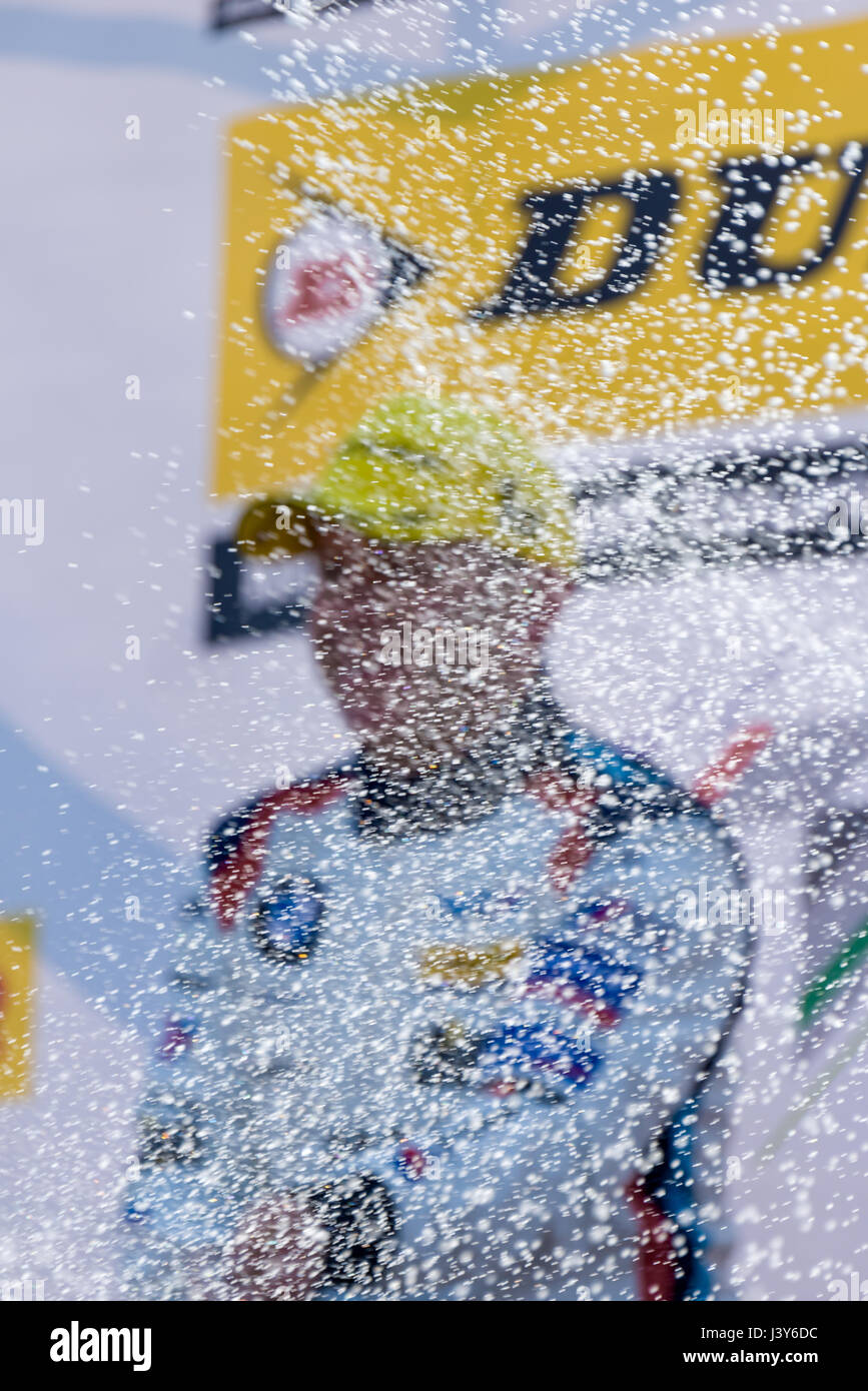 A racing driver at the British Touring Car Championship celebrates his victory by spraying Champagne from the podium. - Stock Image