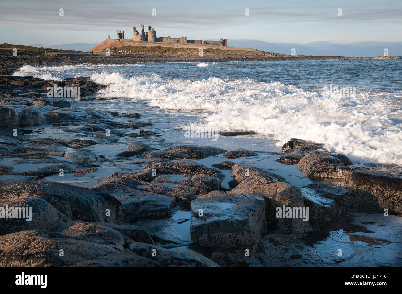 Dunstanburgh Castle on its Whin Sill outcrop, seen from the south. The castle, built in the 14th century, fell into - Stock Image