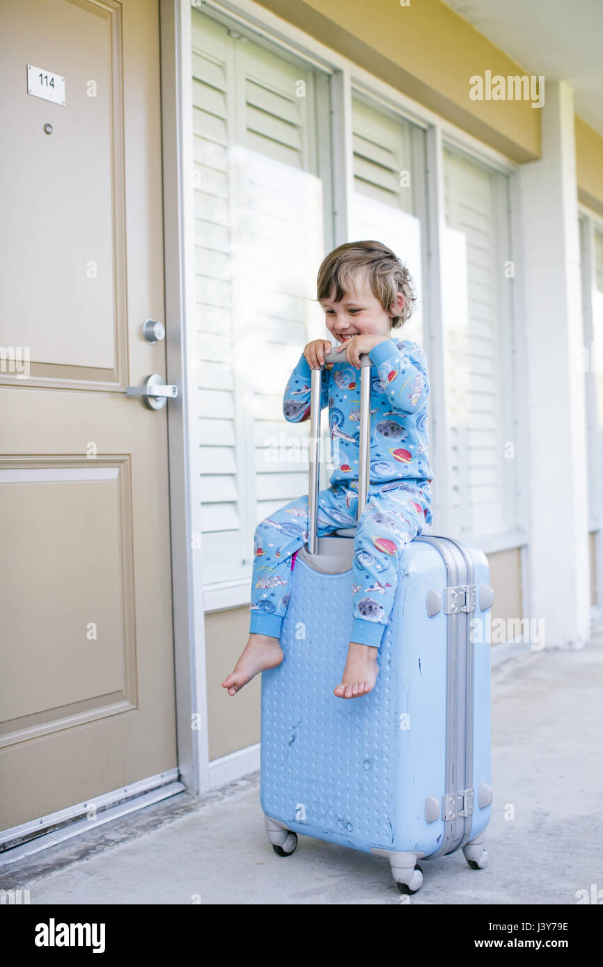Boy in pyjamas sitting on wheeled suitcase outside chalet - Stock Image