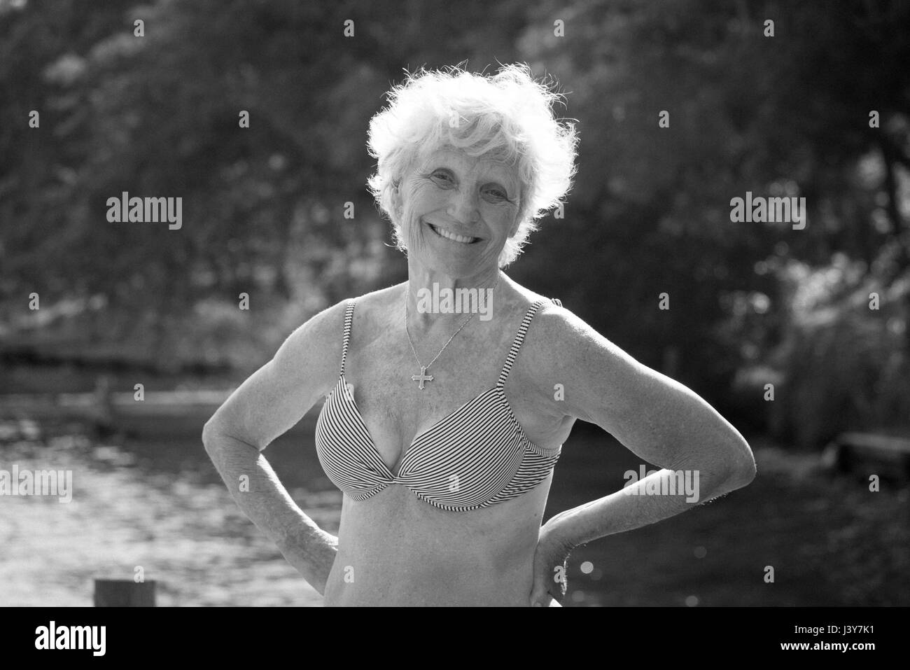 Portrait of senior woman in bikini looking at camera smiling - Stock Image