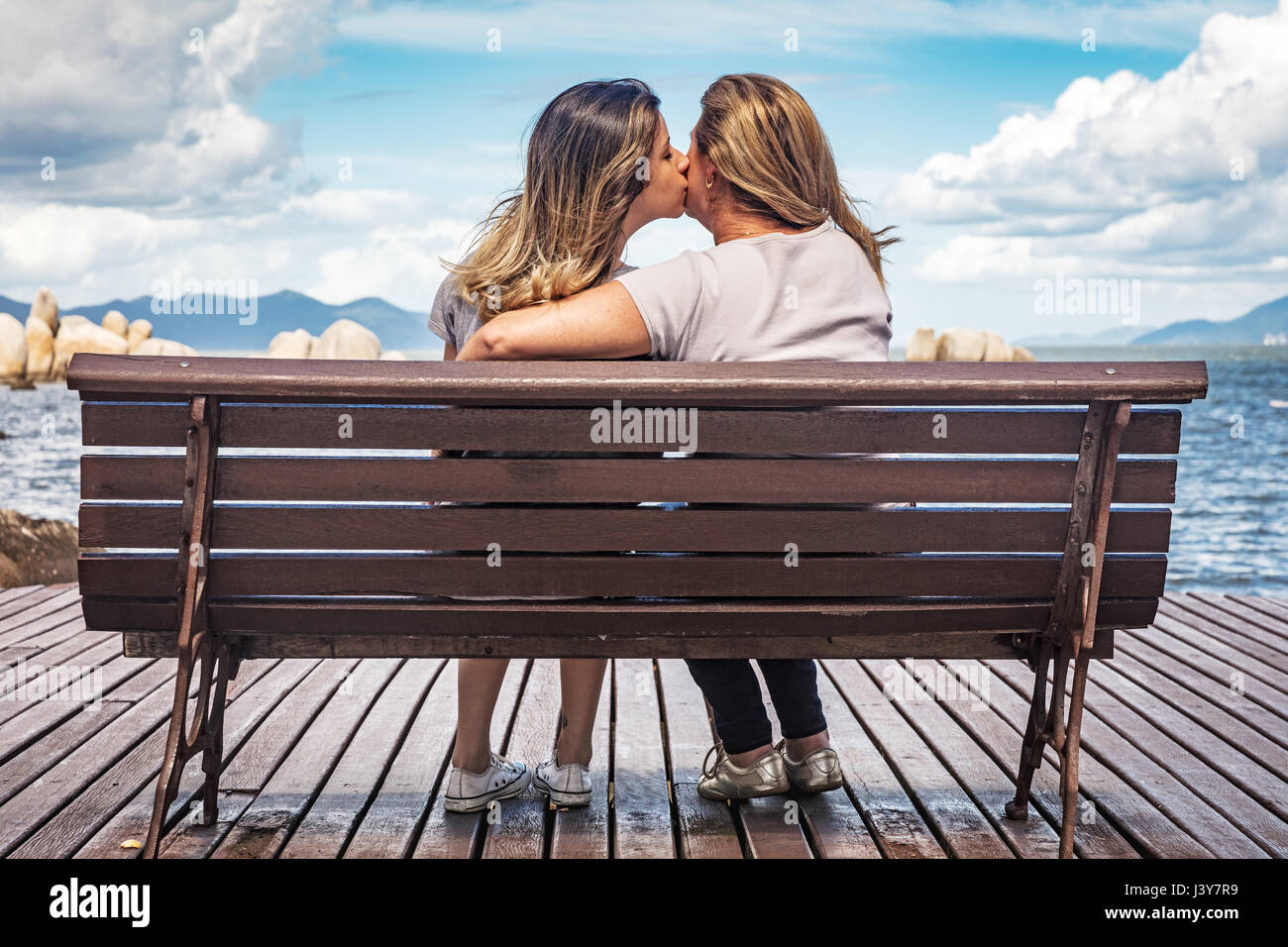 Rear view of mother and daughter on park bench kissing - Stock Image