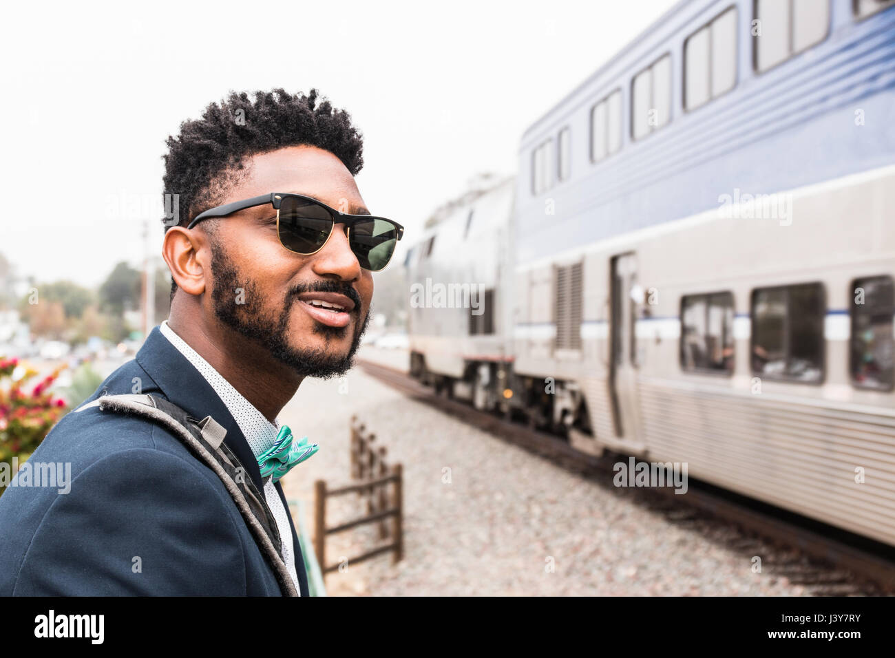 Young businessman in bow tie watching train arrive at platform - Stock Image