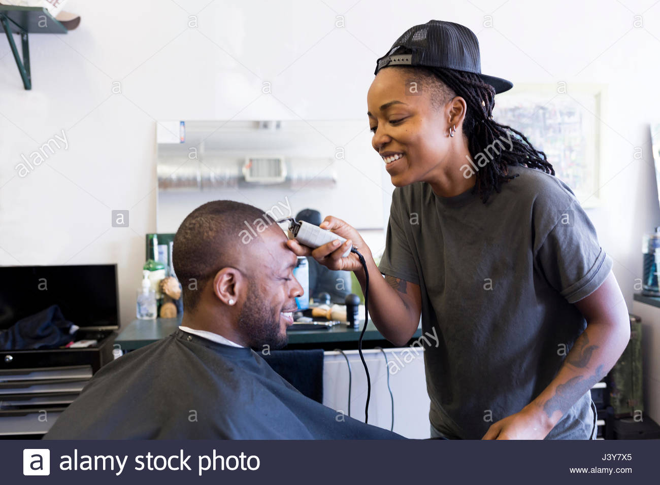 Female barber using hair clippers on male customer in barber shop - Stock Image