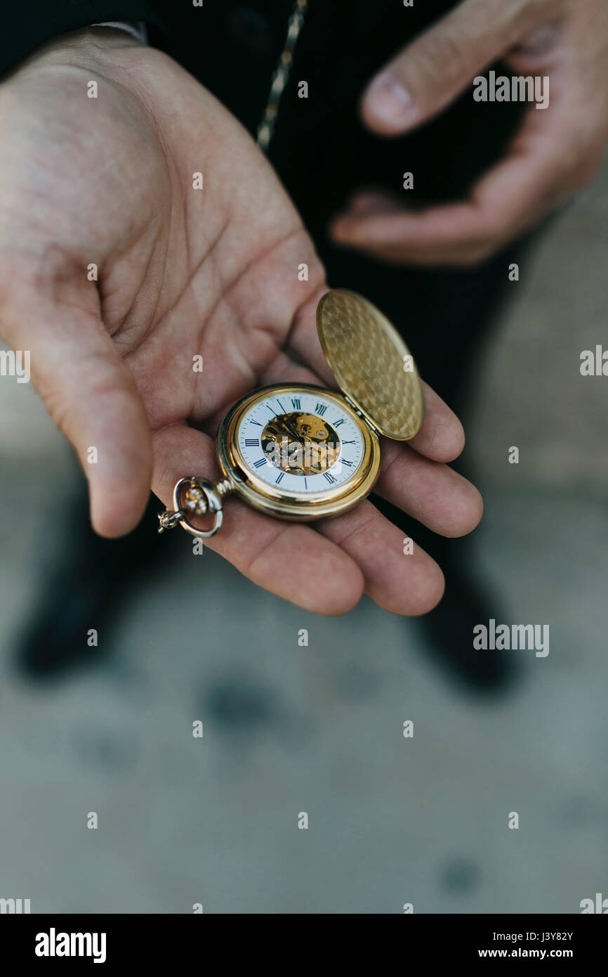 Man wearing suit, holding pocket watch in hand, elevated view, close-up Stock Photo