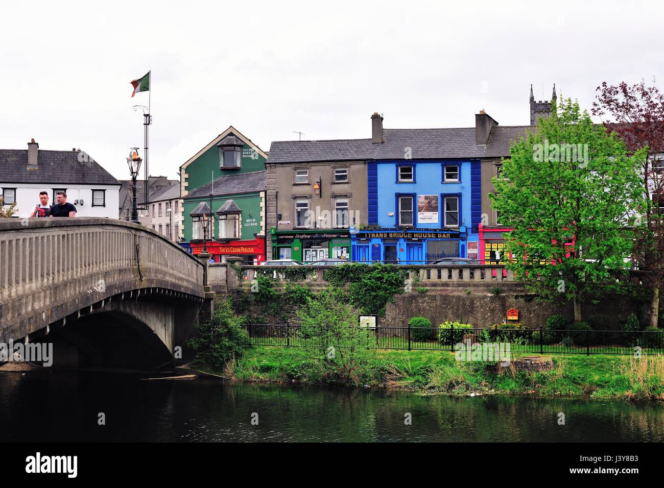 Colorful shops and buildings beyond the River Nore in Canal Square in  Kilkenny, Ireland. An ancient city in County - Stock Image