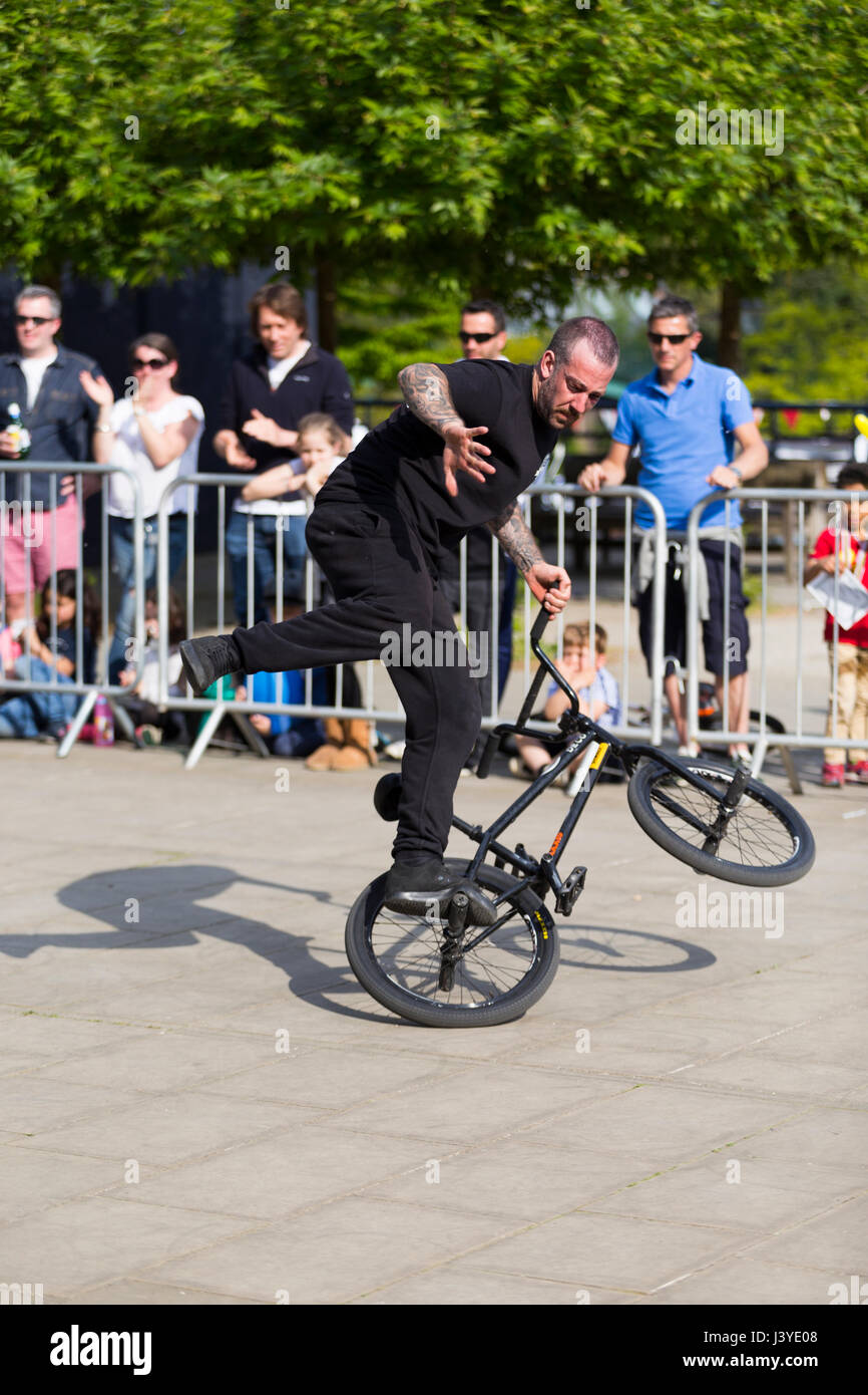 A stunt cyclist riding a bike / cycle during an exhibition performing stunts / wheelies and other trick / tricks. - Stock Image