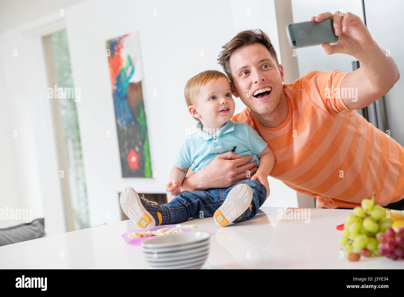 father and toddler son taking selfie in kitchen at home Stock Photo