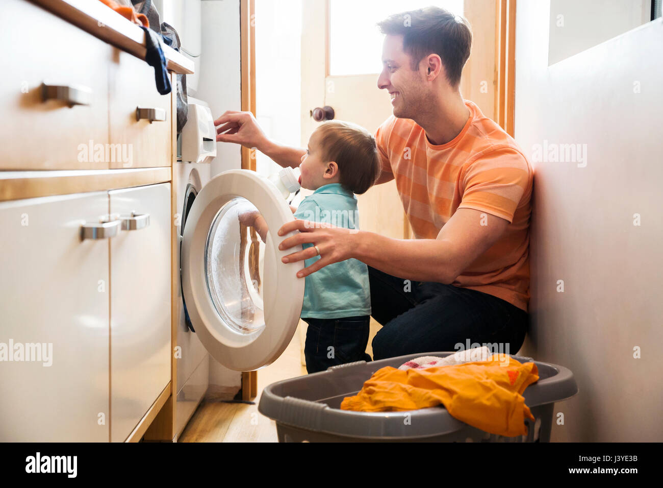 Father and toddler son doing laundry at home - Stock Image