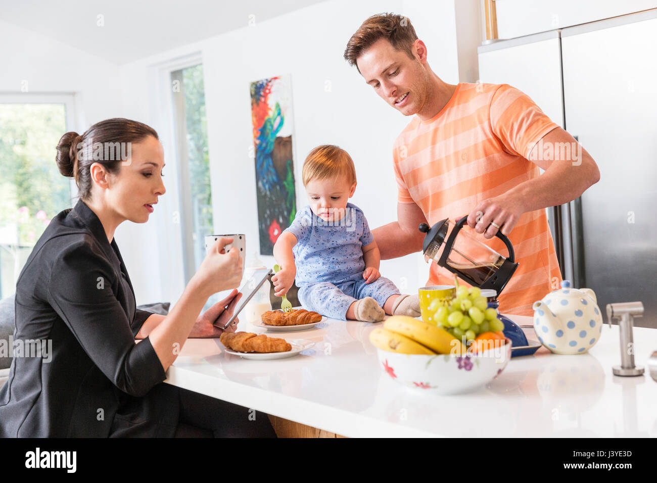 Father makes breakfast for working mum and toddler son - Stock Image