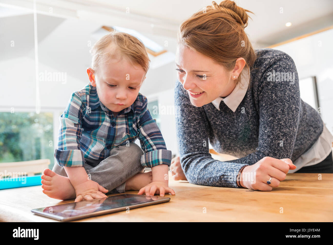 mother and toddler son looking at tablet at home - Stock Image