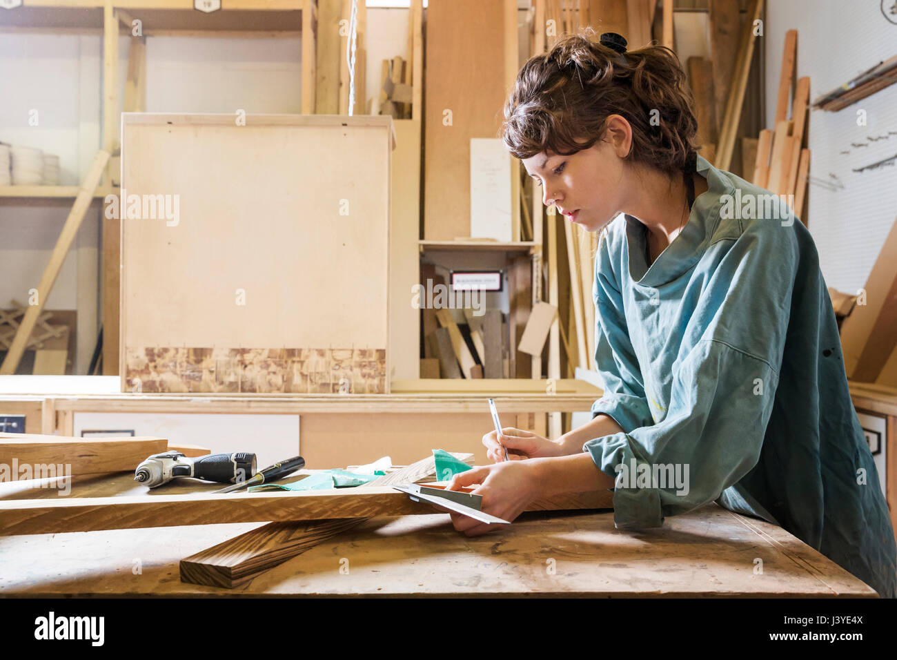 Young woman measuring wood in a workshop - Stock Image