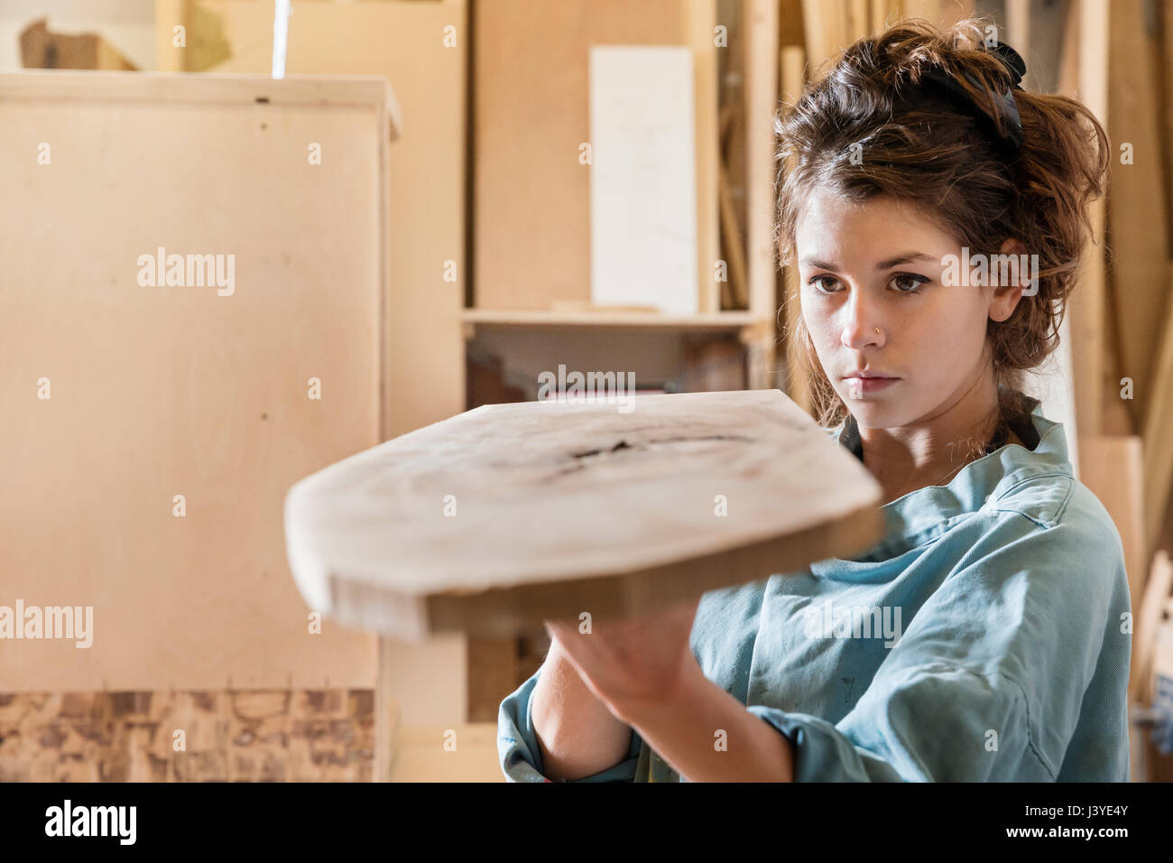 Young woman examining wood sample in a workshop - Stock Image