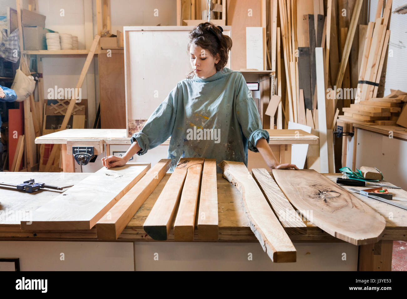 Young woman choosing wood from a selection in a workshop - Stock Image