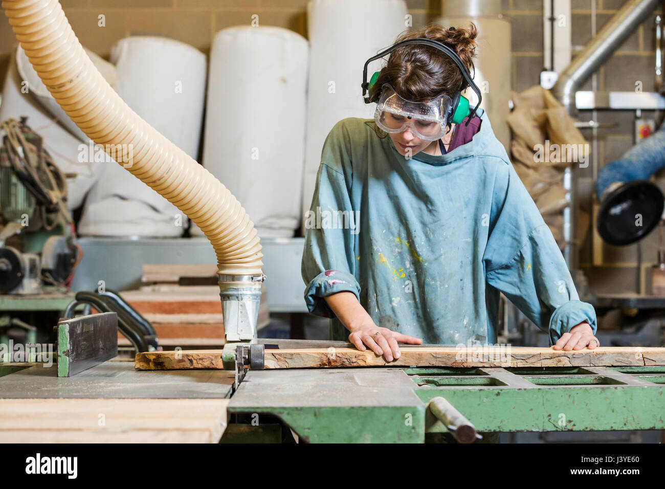 Young woman using machinery in a wood workshop - Stock Image