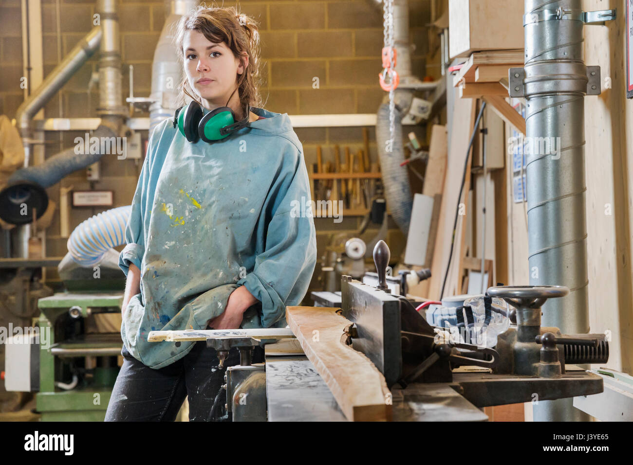 Portrait of young woman next to machinery in wood workshop - Stock Image