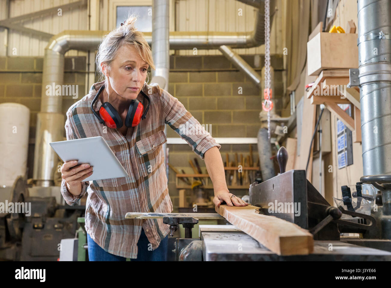 Woman consulting instructions on tablet while using machinery in wood workshop - Stock Image