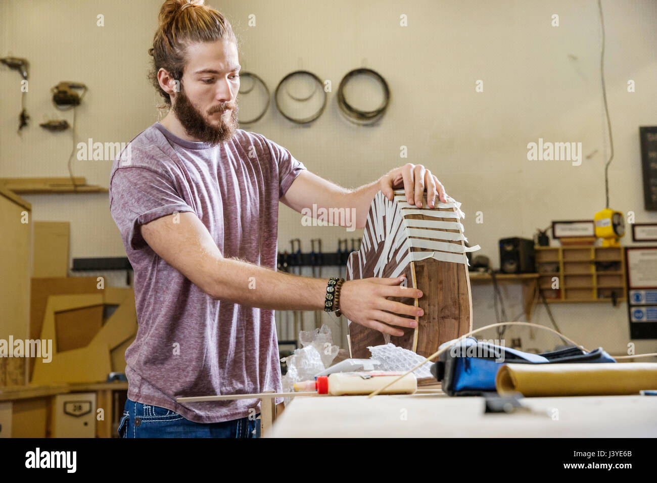 Young man constructing an acoustic guitar in a workshop - Stock Image