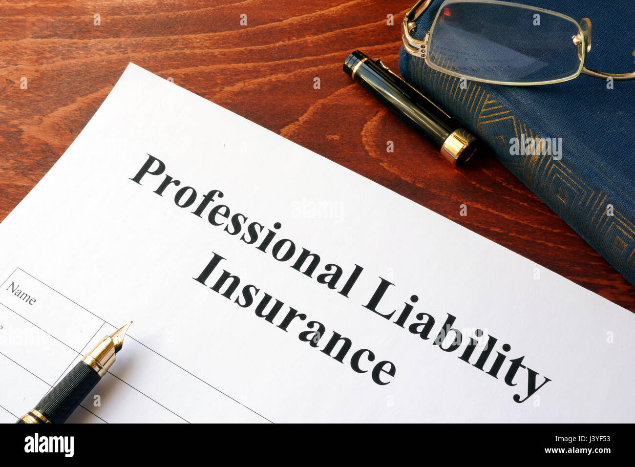 Professional liability insurance policy on a table. - Stock Image