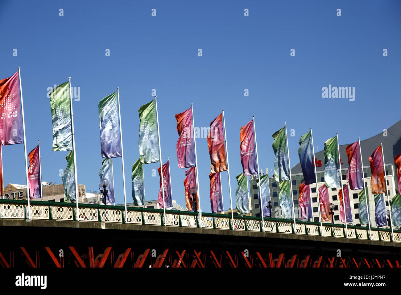 Flags flying over Pyrmont Bridge, Darling Harbour, Sydney - Stock Image