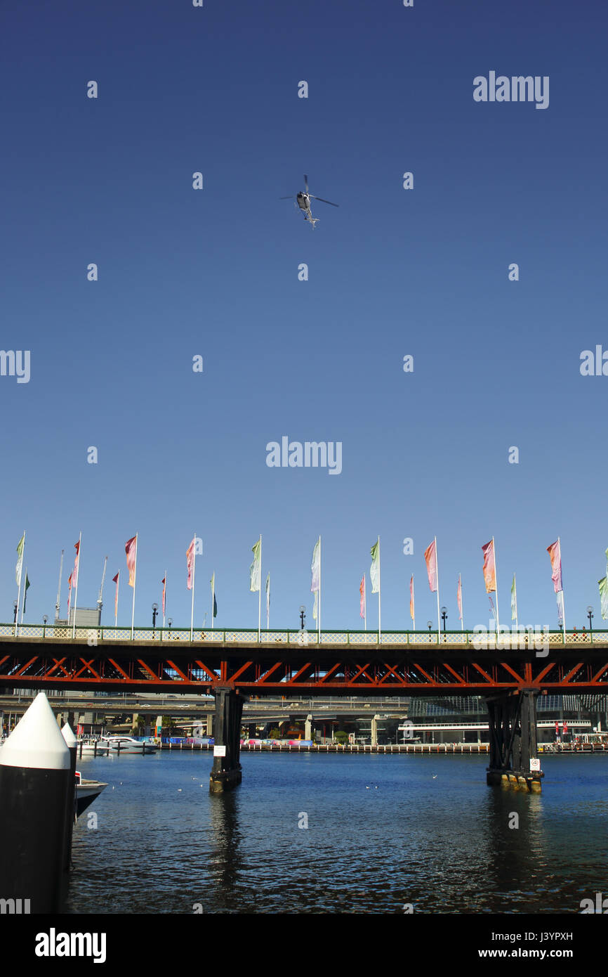A sightseeing helicopter flies above the Pyrmont Bridge at Darling Harbour, Sydney. There is plenty of room for - Stock Image