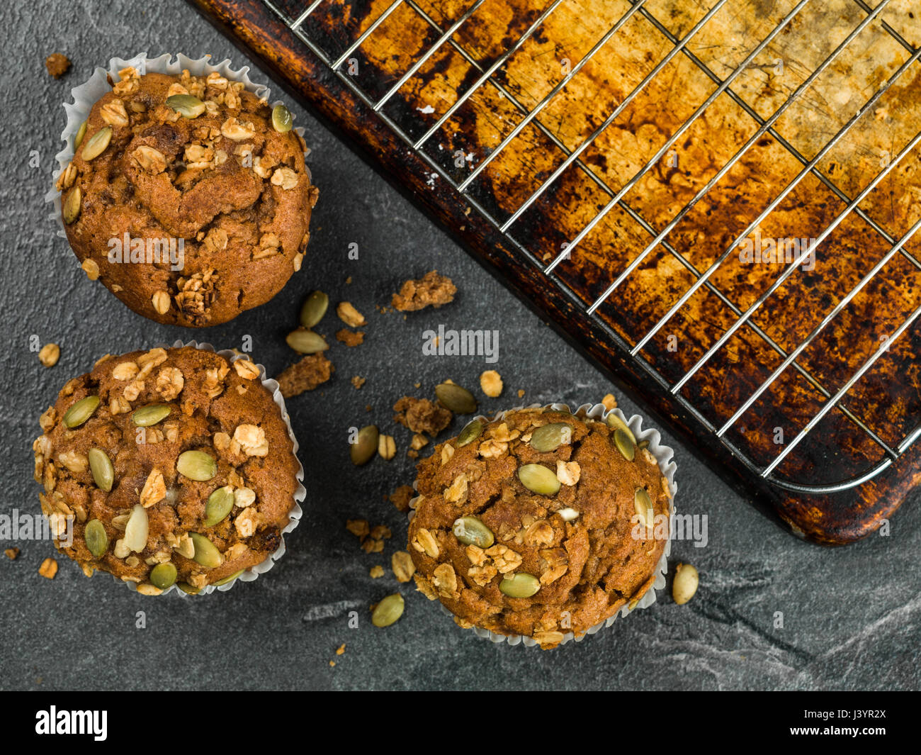 Spiced Carrot Muffin Cakes With Granola and Pumpkin Seeds Against a Black Tile Background Stock Photo