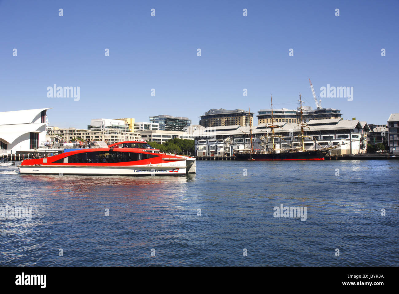 A 'Captain Cook Cruises' catermaran passing a tall ship as it leaves Darling Harbour, Sydney, Australia - Stock Image