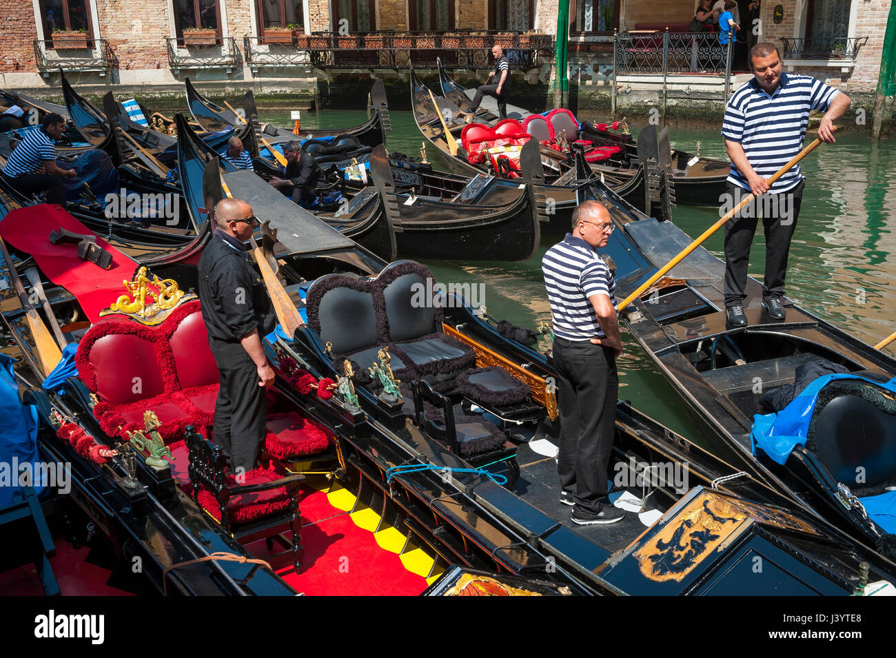 VENICE - APRIL 21, 2013: Venetian gondoliers work in the traditional Bacino Orseolo gondola parking lot behind the - Stock Image