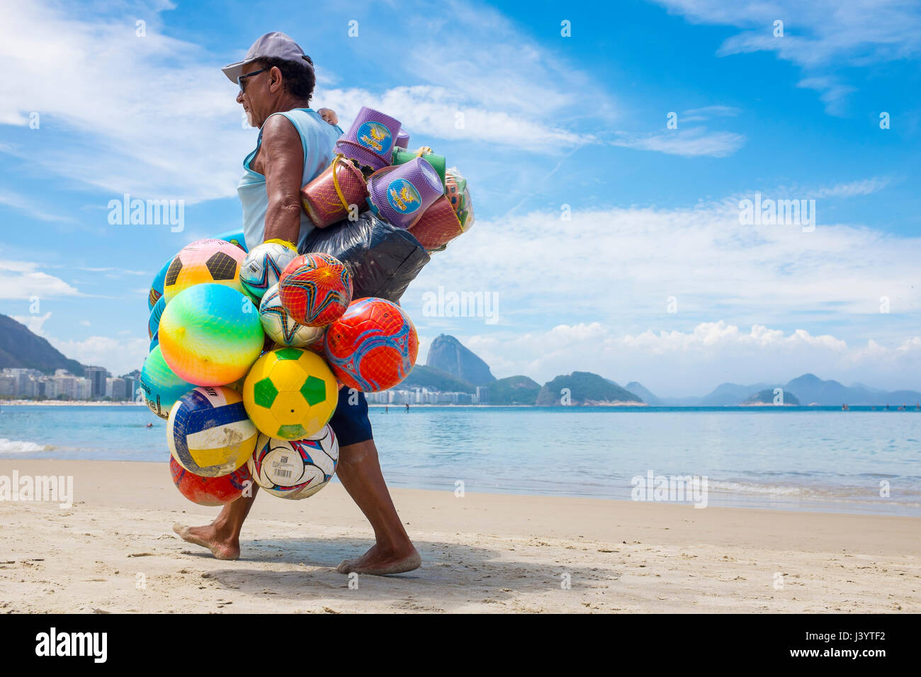 RIO DE JANEIRO - FEBRUARY 10, 2017: Brazilian beach vendor walks along Copacabana Beach looking for customers for - Stock Image