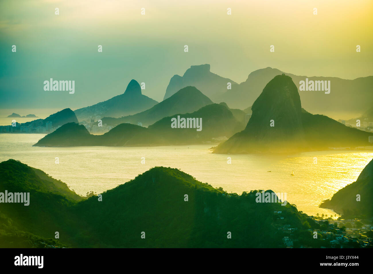 Golden sunset scenic view of the mountainous skyline of Rio de Janeiro, Brazil with Guanabara Bay - Stock Image