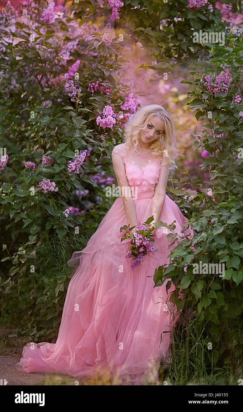 Beautiful woman enjoying lilac garden young woman with flowers in beautiful woman enjoying lilac garden young woman with flowers in green park cheerful teenager walking outdoor soft light style color izmirmasajfo