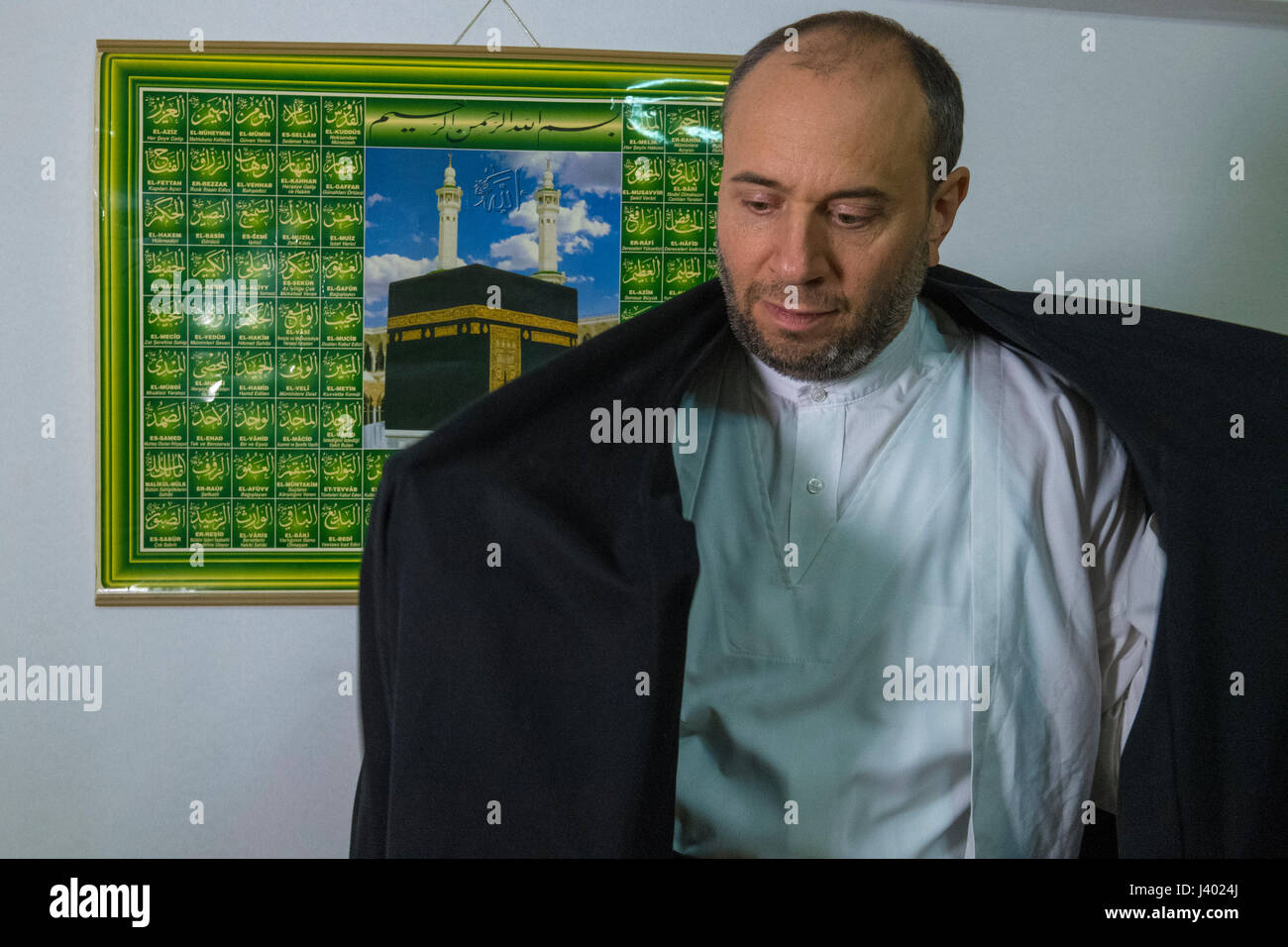 Dervish Robing, Putting on Hirka, black coat, in front of a picture of Kabba, Yaqup Baba of Fatih, Istanbul, TURKEY - Stock Image