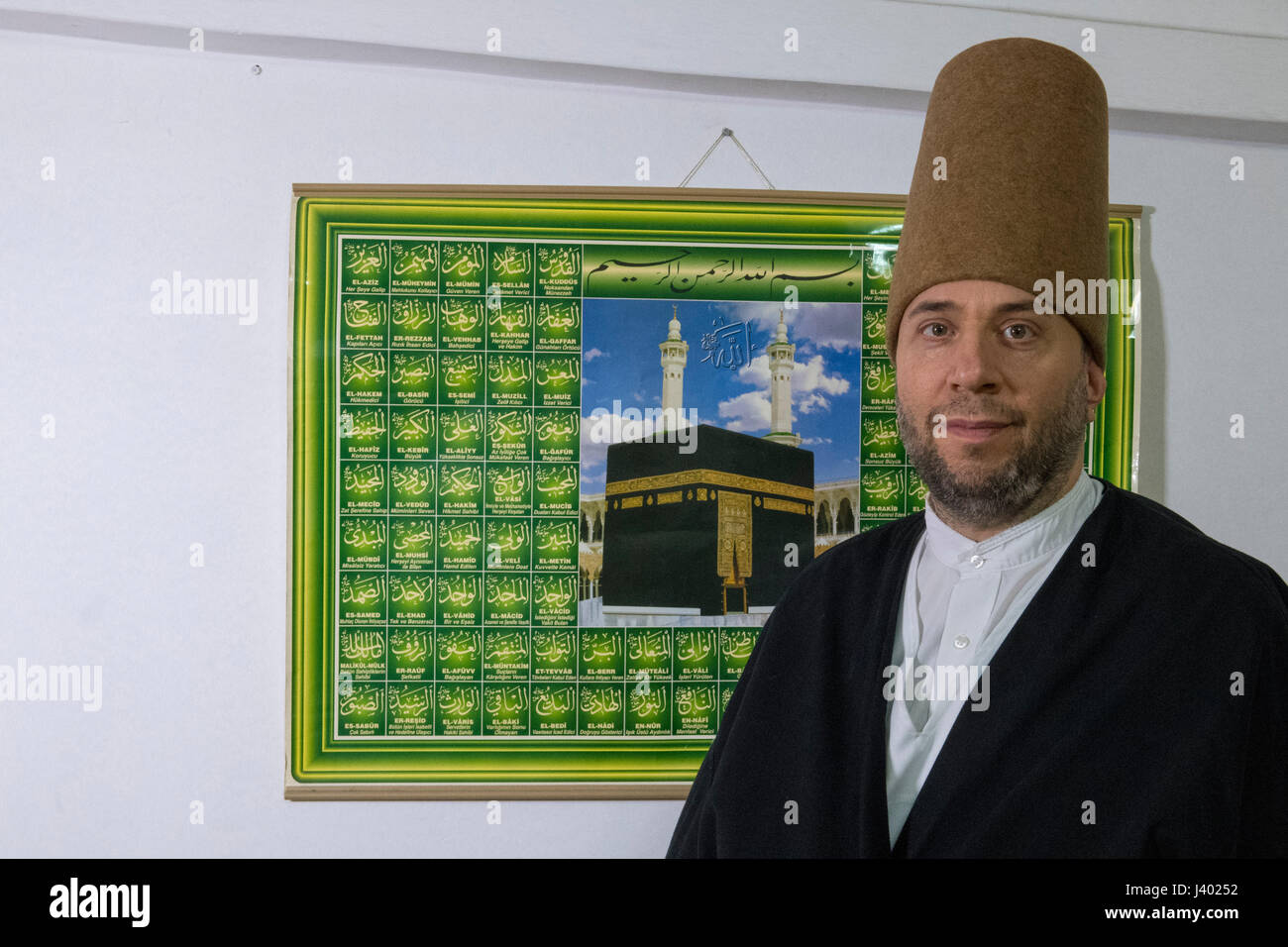 Dervish Robed, Wearing Sikke In Front Of A Picture Of Kabba, Hat Made Of Lamb's Wool, Yaqup Baba of Fatih, Istanbul, - Stock Image