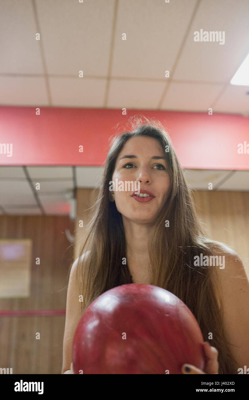 A young woman bowling. - Stock Image