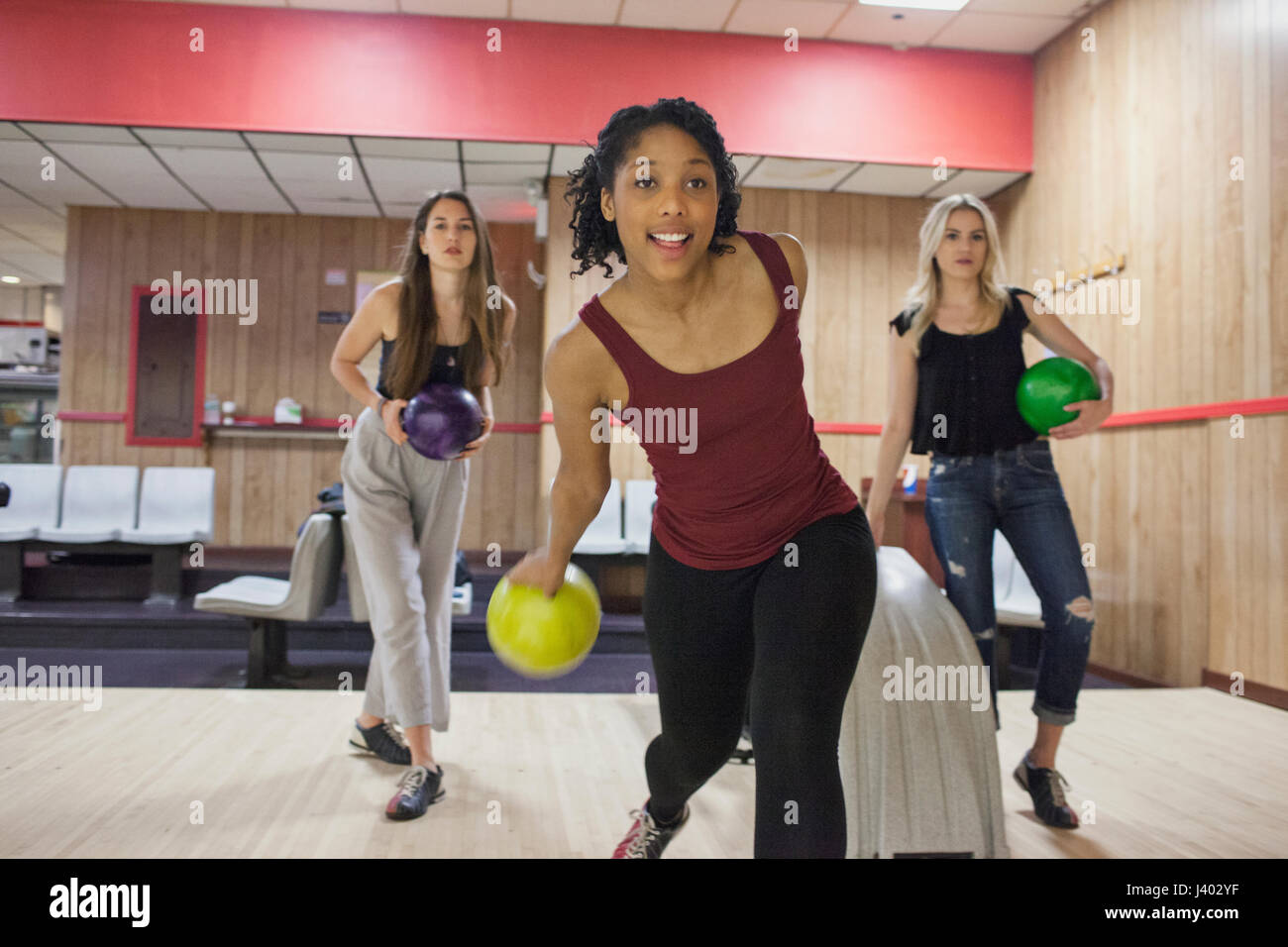A young woman bowling with friends. - Stock Image
