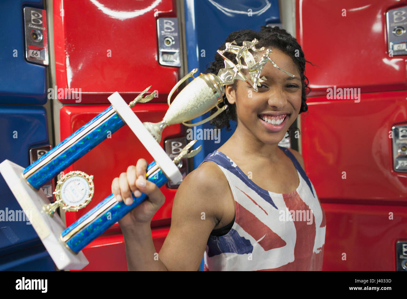 A young woman with a trophy in fornt of red and blue lockers. - Stock Image