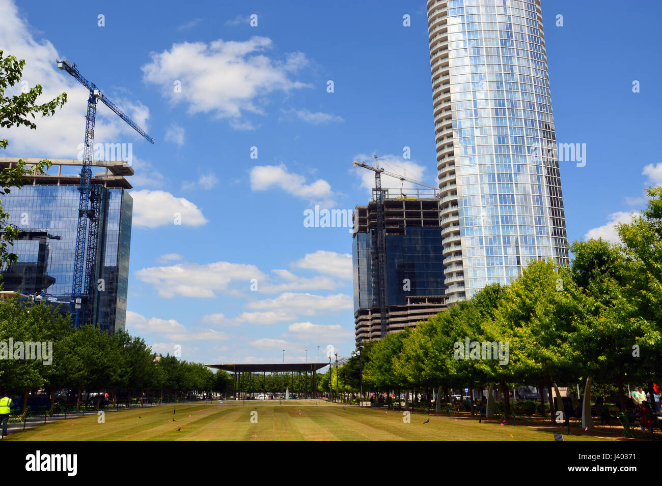 Construction cranes dominate the skyline during a building boom of new apartments and offices in downtown Dallas - Stock Image
