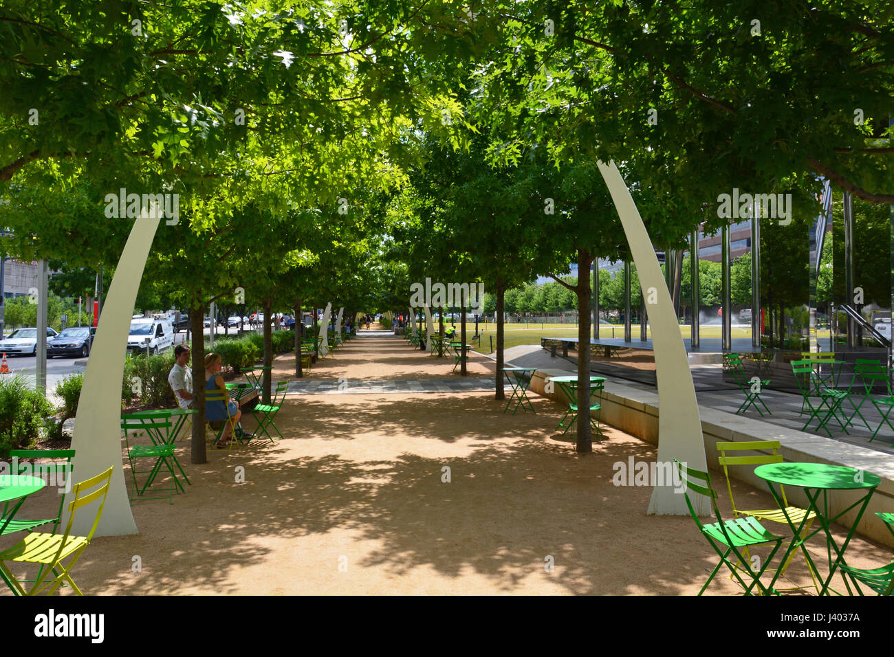 Public seating under oak trees and decorative arches line the promenade at Klyde Warren Park located above a recessed Stock Photo