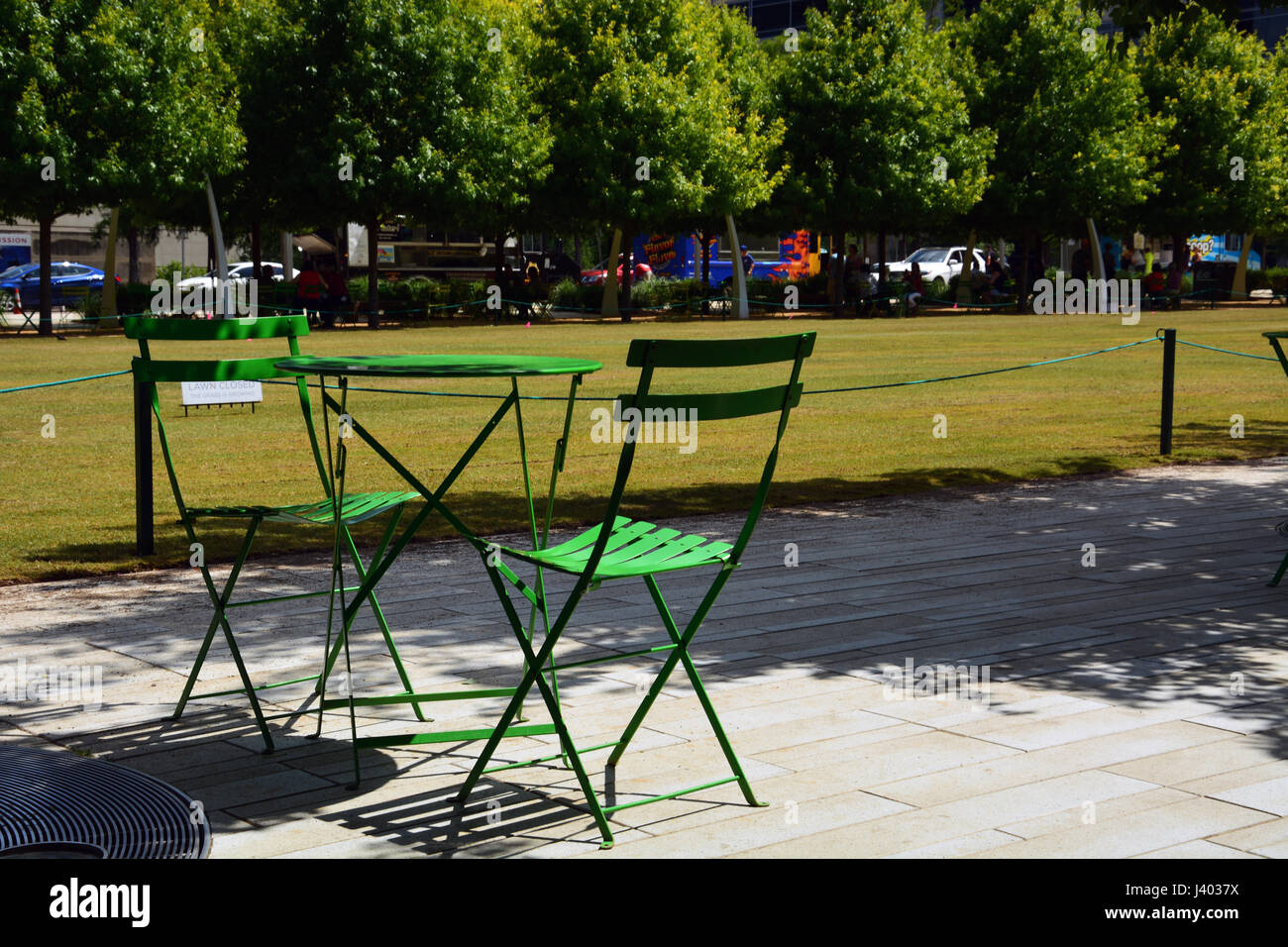 Public tables and chairs line the walkways and tree lined paths around Dallas' downtown Klyde Warren Park built Stock Photo