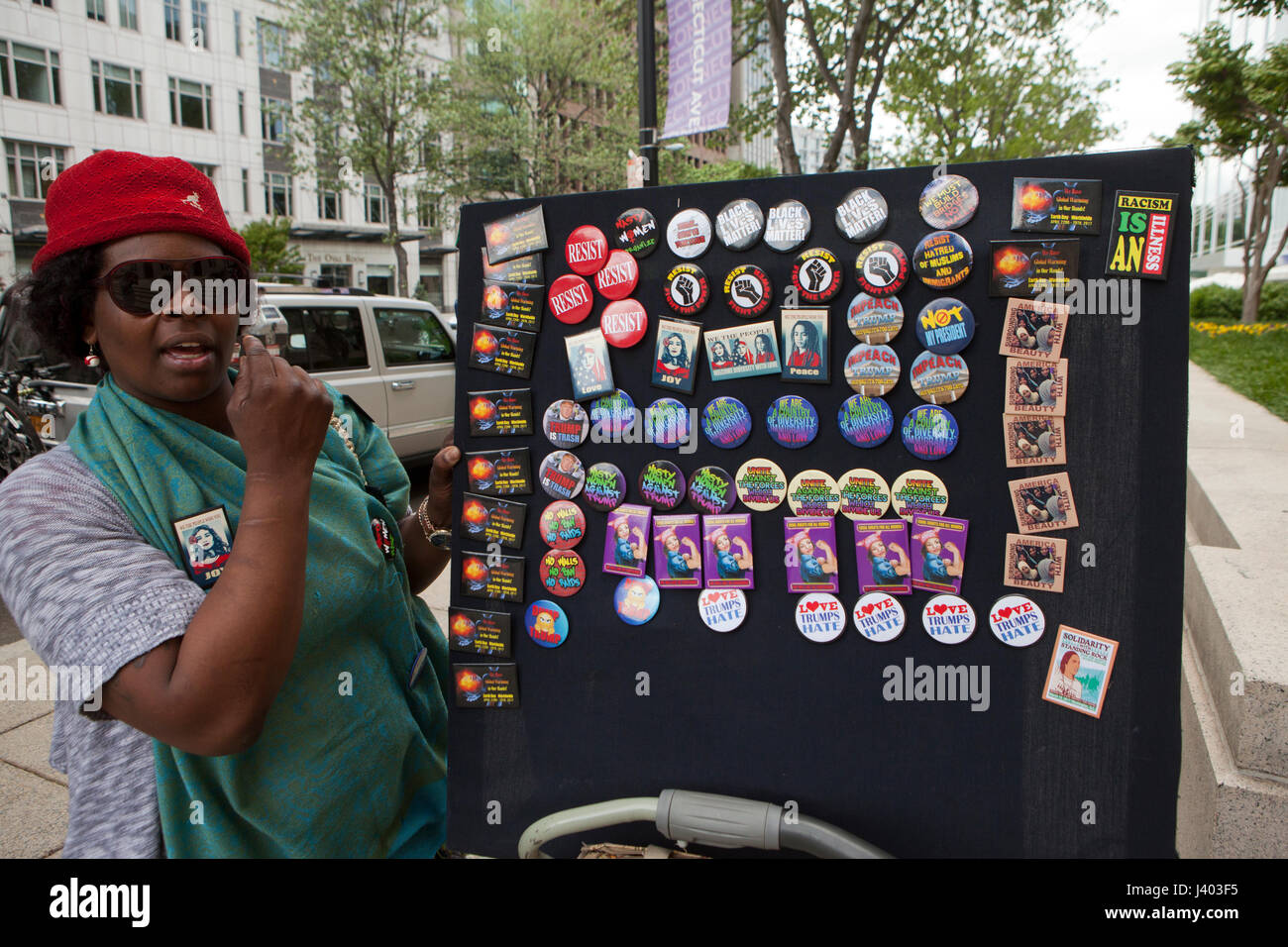 African-American woman selling Liberal issues and feminist movement related buttons on street - Washington, DC USA - Stock Image