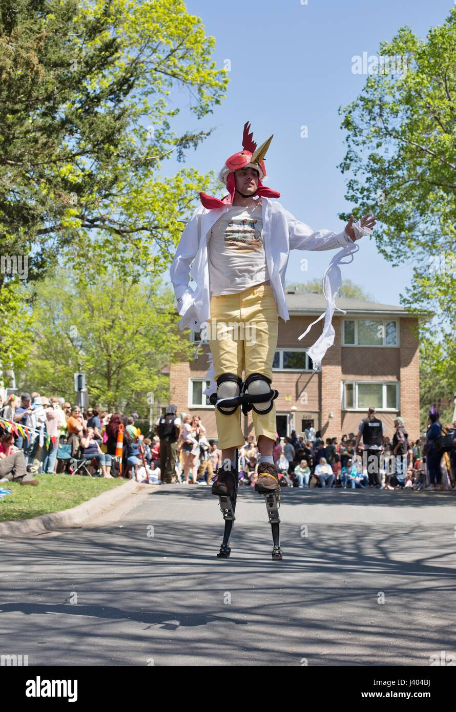 A man bouncing with spring shoes at the Mayday parade in Minneapolis, Minnesota, USA. - Stock Image