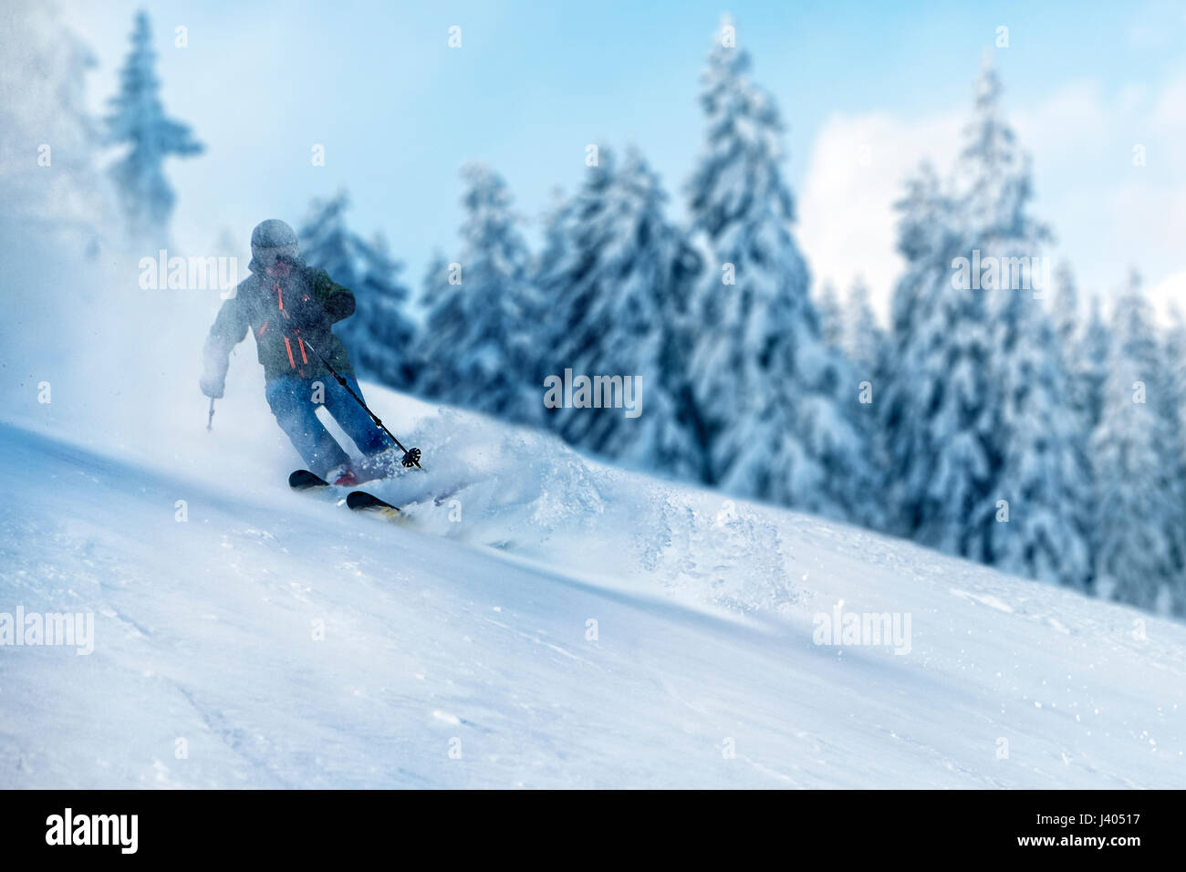 Freerider in backcountry powder snow with fir trees in the background. The skier is surrounded by a snow cloud. - Stock Image