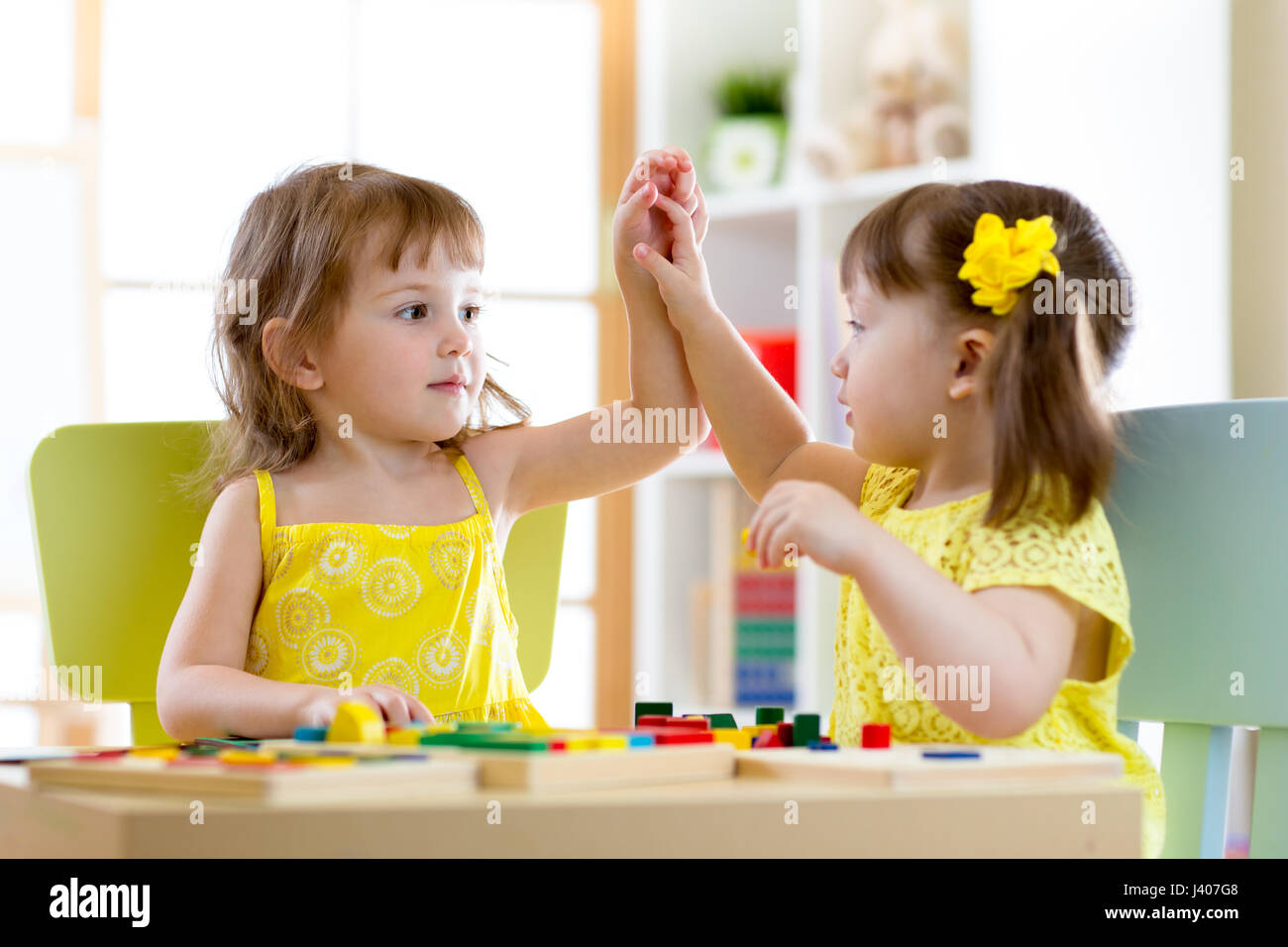 Two cute little girls playing together in daycare Stock Photo