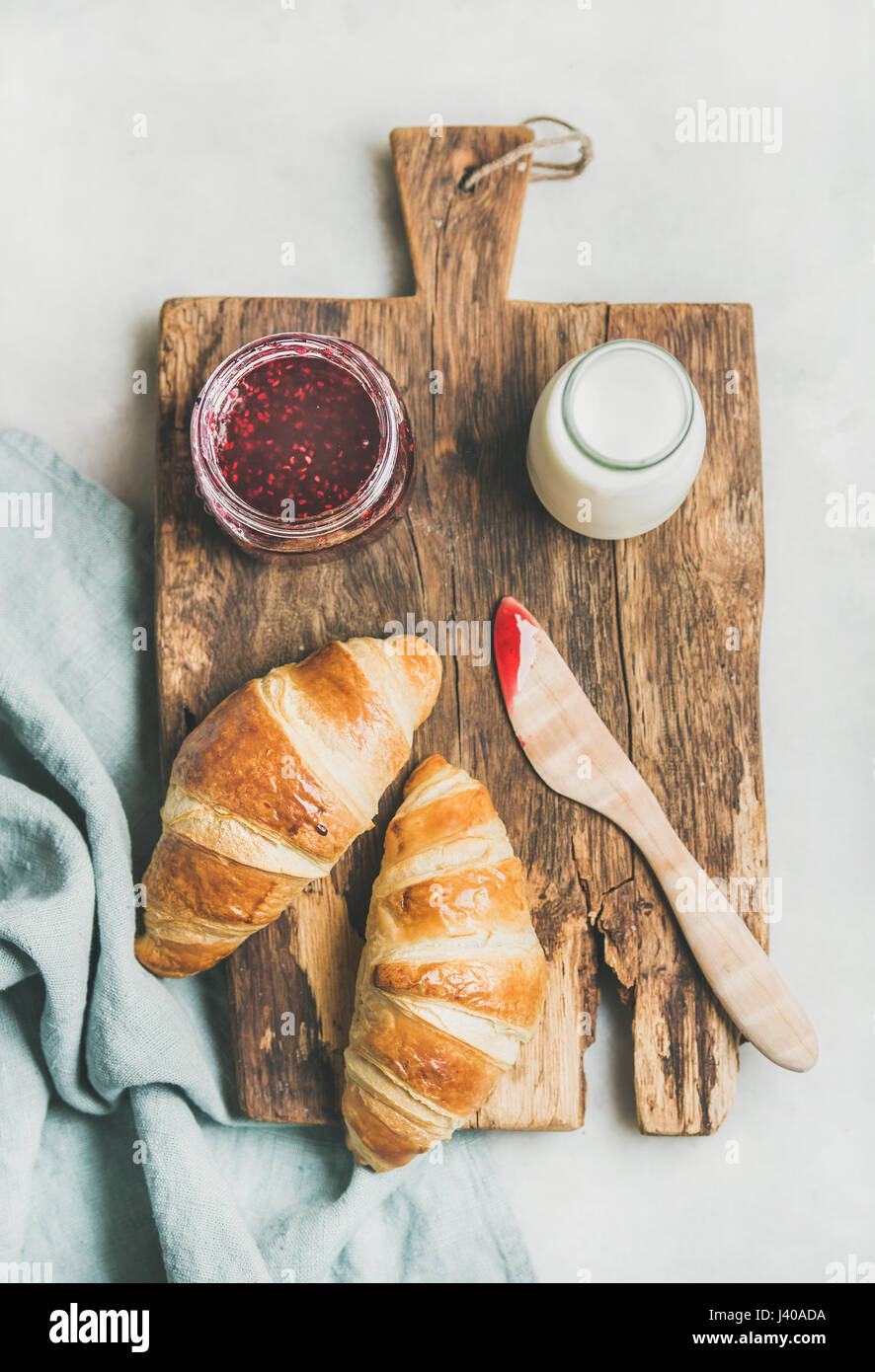 Freshly baked croissants with raspberry jam and milk in bottle - Stock Image