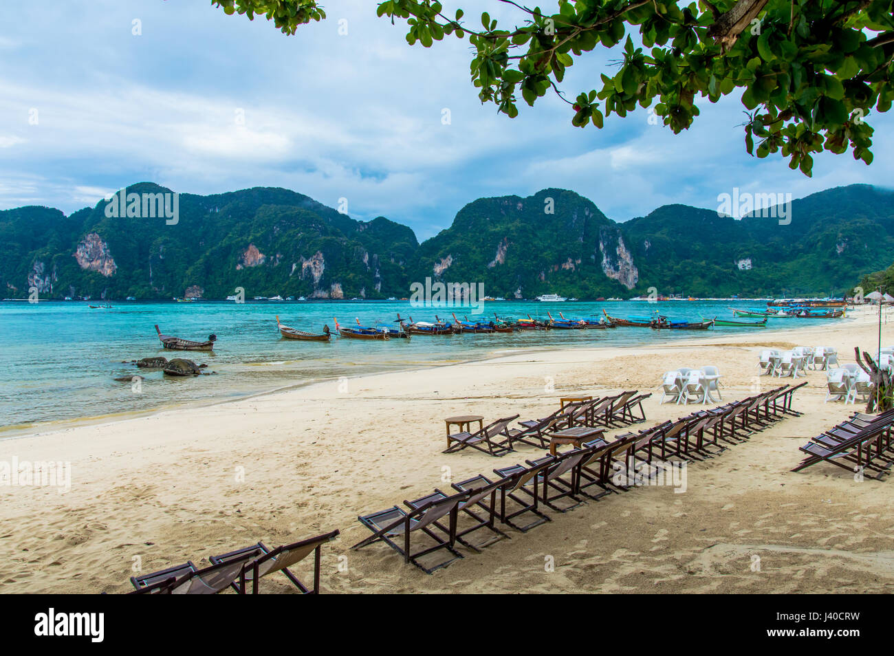 View of Phi Phi island beach bay against longtail boats moored and coast - Stock Image