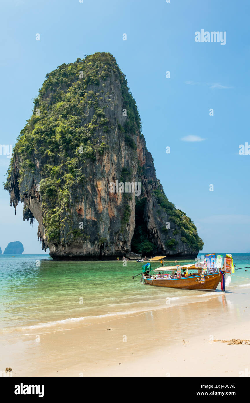 Scenic View of Beach and longtail boat against eroded mountain by sea - Stock Image
