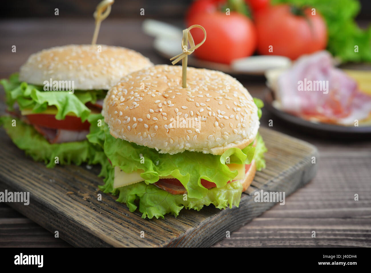Burger with bacon, tomato and cheese on wooden table close up - Stock Image