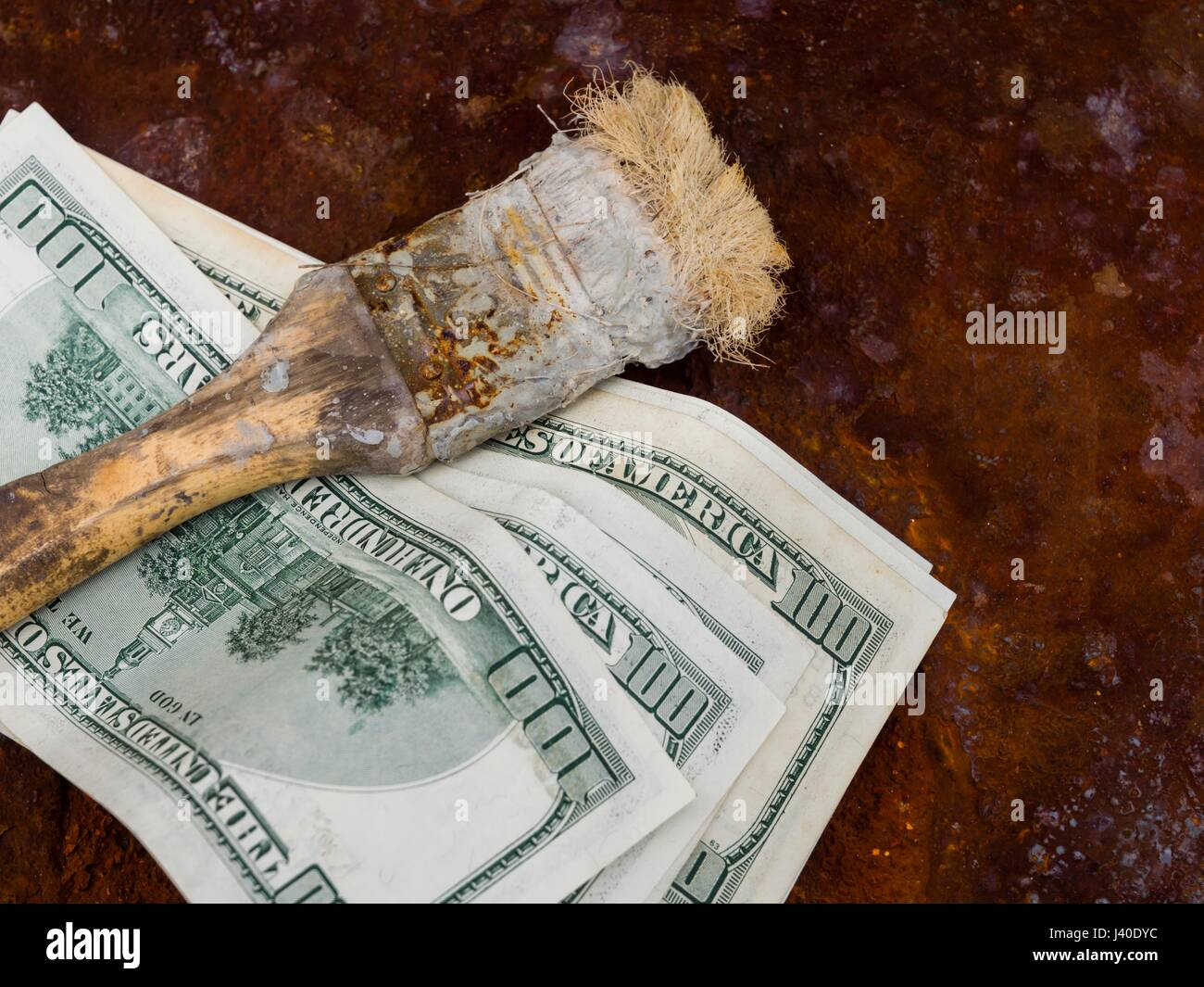 Dirty money dollars and rotten old hand-brush several bunch lying on rusty iron floor - Stock Image