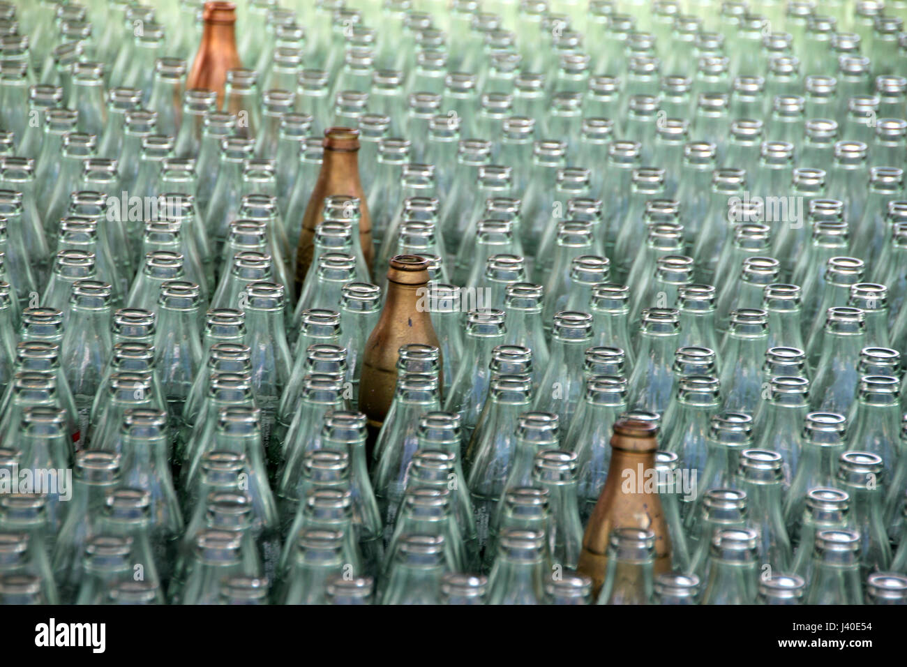 Glass bottles together with select golden bottles. Ring toss game. - Stock Image