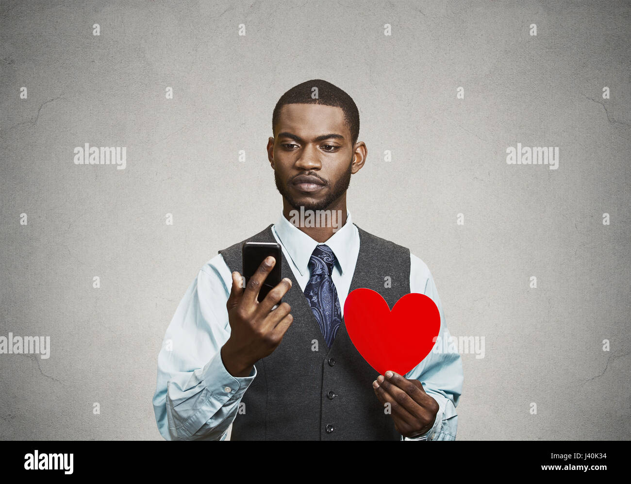 Closeup portrait serious, thoughtful young man reading news, text message on his smart phone, holding red heart - Stock Image